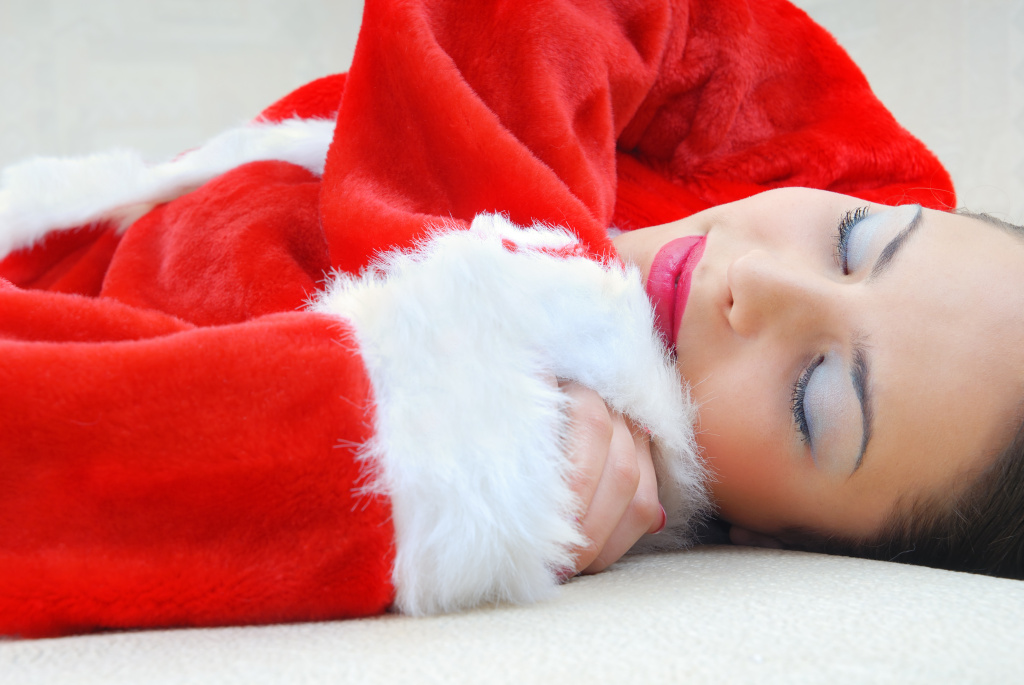 Sleeping pretty woman in the red costume of Santa Claus